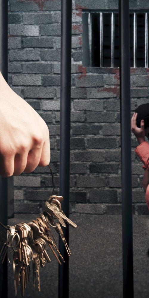 prison guard with keys outside dark prison cell