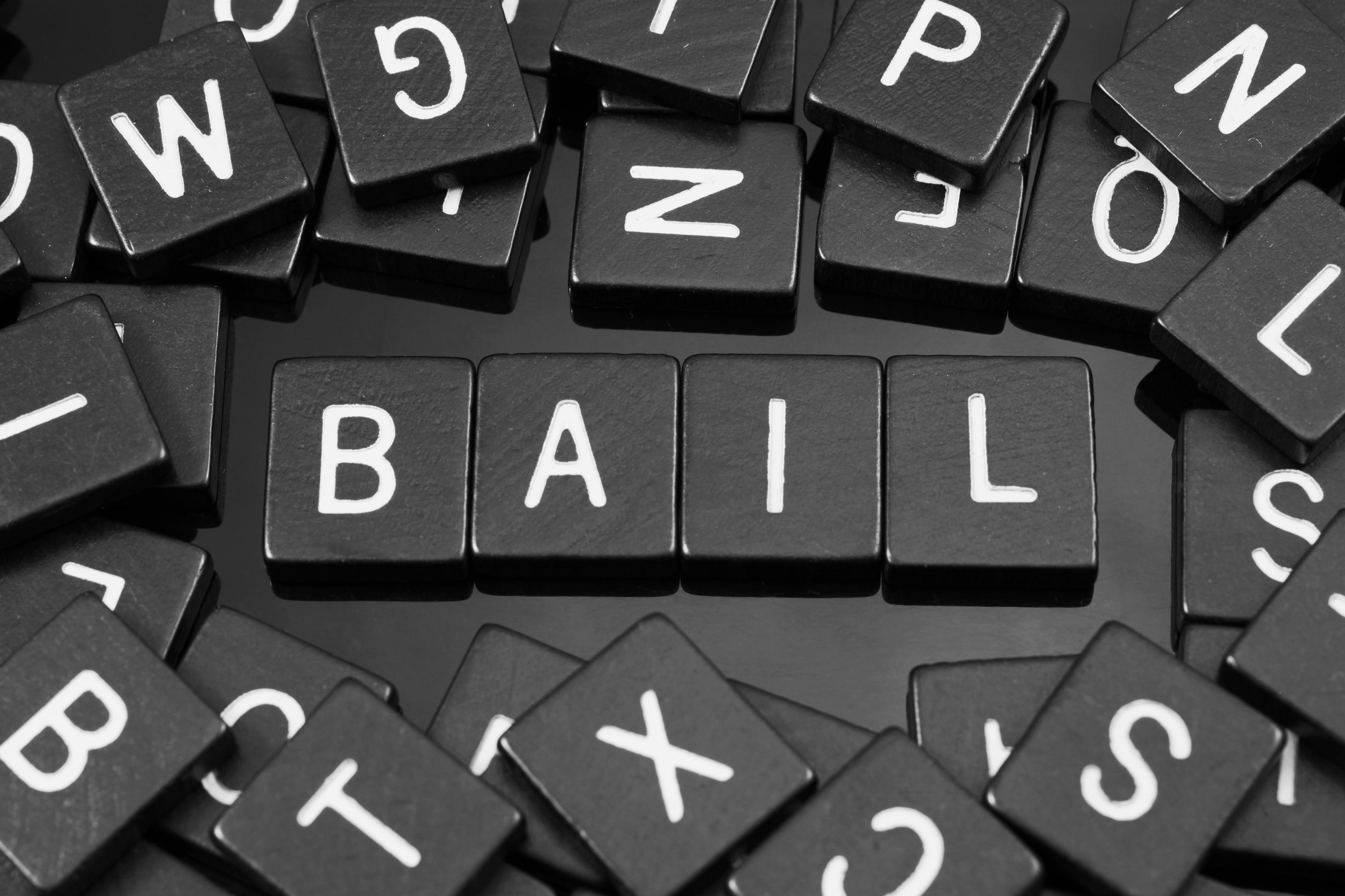 """black letter tiles spelling the word """"bail"""" on a reflective background"""