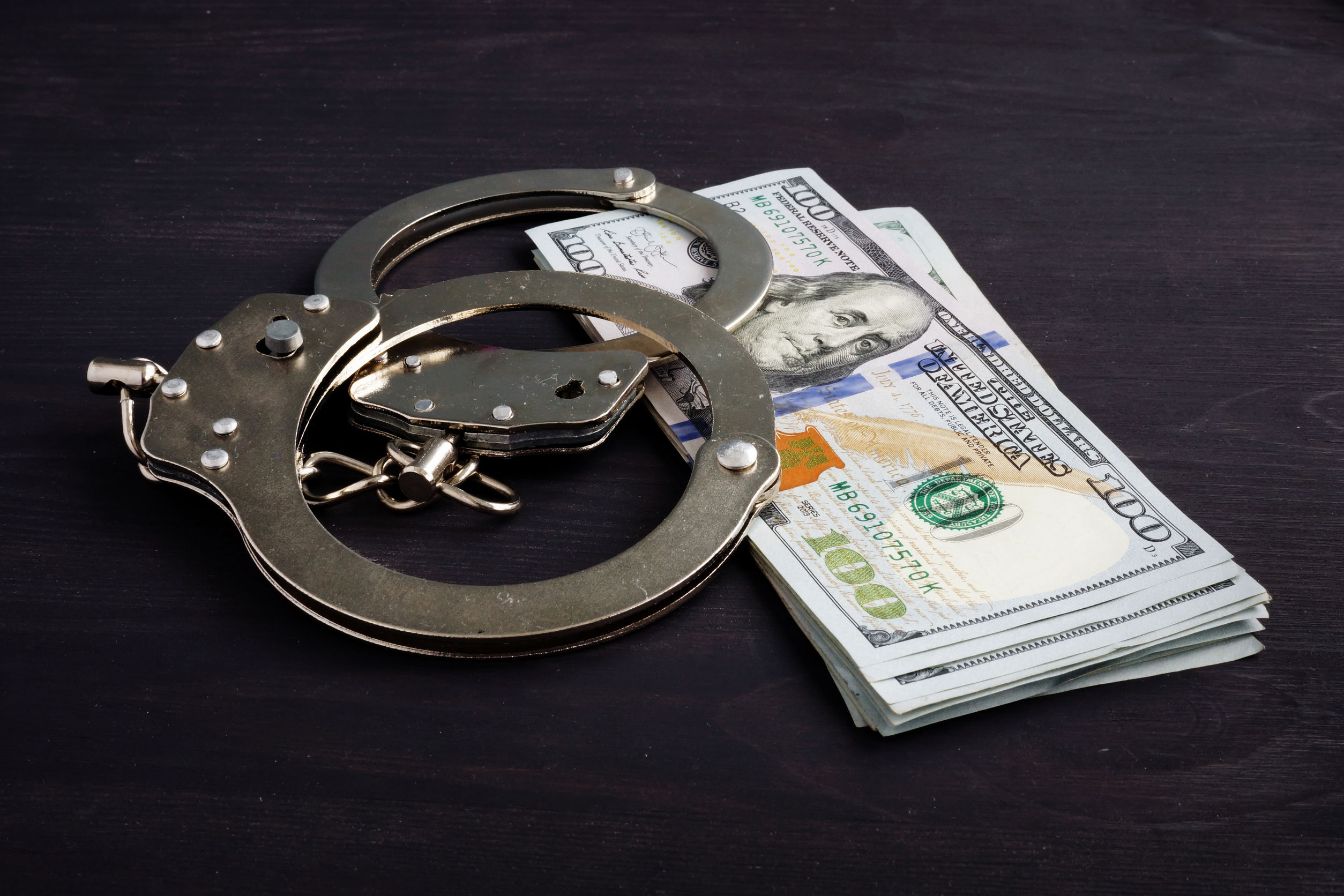 Handcuffs and money. Dollars for bail bonds.