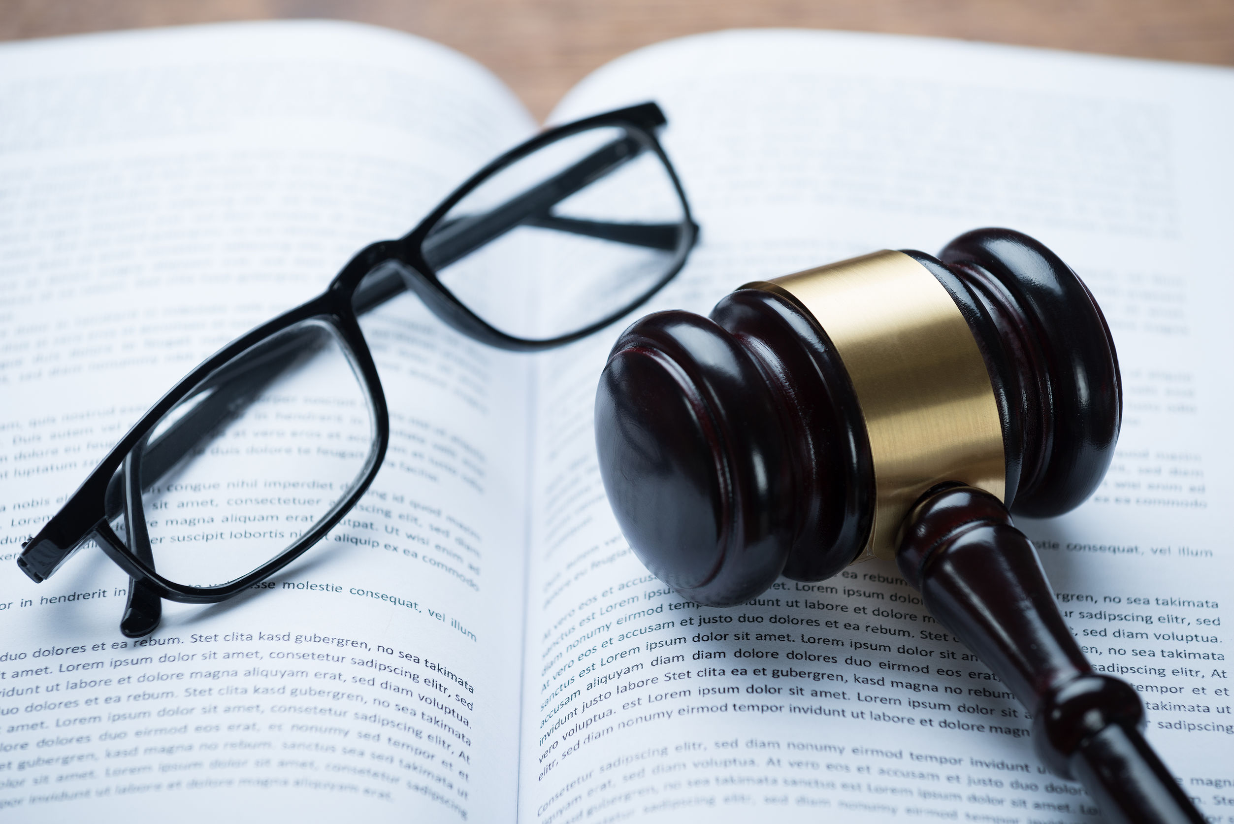 High angle view of mallet and eyeglasses on open legal book in courtroom